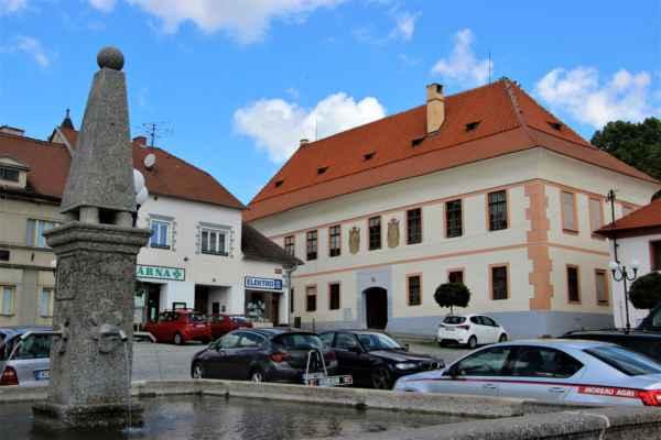 Bavorov - pohled na budovu Panský dům, kterému se říká také zámek, pochází ze 16. století. Nahlížíme přes čtvercovou kašnu z roku 1742.