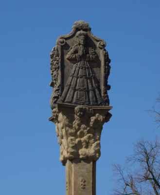 Na vrcholové desce je z východní strany směrem k faře reliéf prosebnice, který představuje Pannu Marii Polickou. Na západní straně se nachází plastická kopie oltářního obrazu z kostela Panny Marie Vítězné na Bílé Hoře v Praze.
