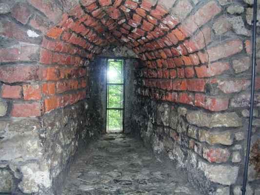 Středověká střílna a zeď široká a dlouhá jako lidské tělo