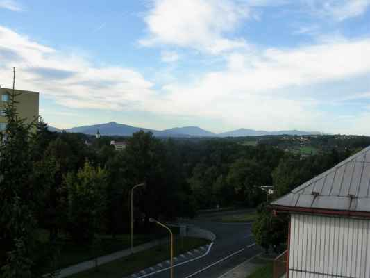 Pohled z Havířova na pět vrcholů Beskyd. Zleva od žlutého vysokého domu: Travný (nejde skoro vidět) Lysá hora (za kostelem) Smrk Kněhyně Radhošť